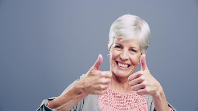 optimism är den tro som leder till prestation - mature women studio grey hair bildbanksvideor och videomaterial från bakom kulisserna