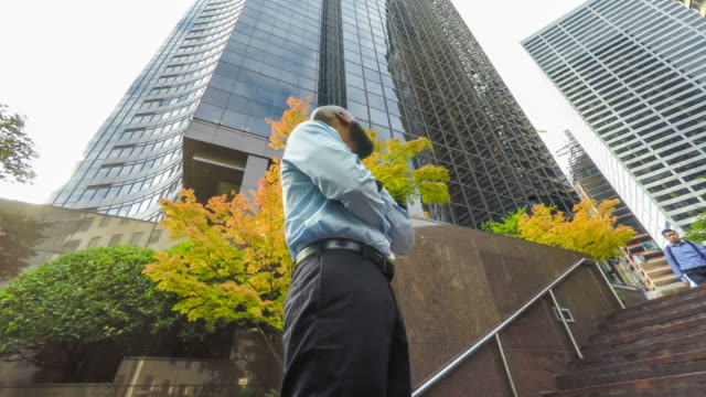 Optimistic Businessman Looking up at Tall Buildings Surrounding Him 4k clip of an African American businessman standing among tall buildings, looking up optimistically office park stock videos & royalty-free footage