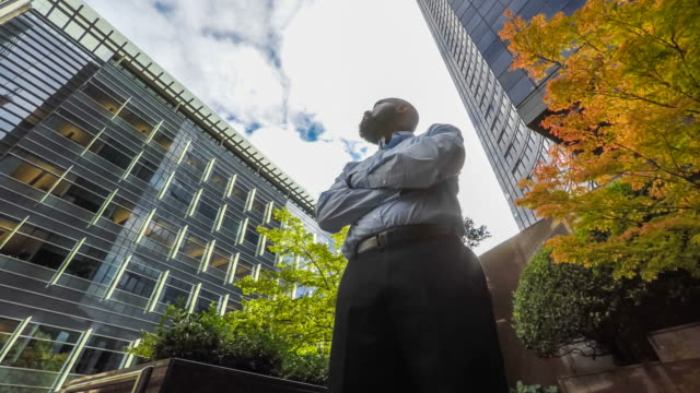 Optimistic Businessman Looking up at Tall Buildings Surrounding Him