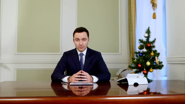Optimistic charming president looking at camera and speacking before Christmas video