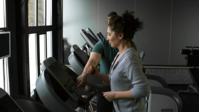Optimistic Woman Exercising on Treadmill in Gym