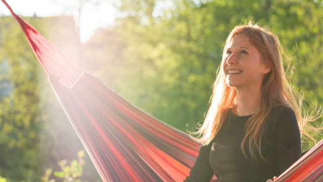 Optimistic woman swinging in a hammock in backyard in summer video