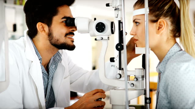 optometrist checking patient eyesight and vision correction - optometrist stock videos and b-roll footage