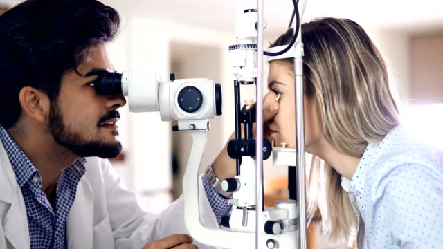 optometrist checking patient eyesight and vision correction video