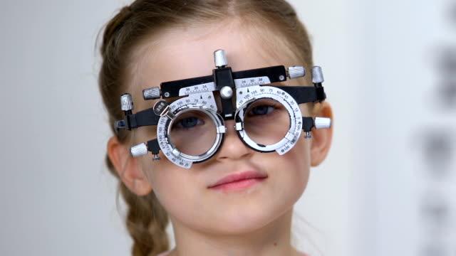 vidéos et rushes de optométriste choisissant la lentille pour le patient d'enfant utilisant le phoropter, consultation de clinique - réfracteur