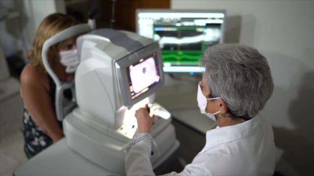 optometrist untersucht patientenaugen - augenheilkunde stock-videos und b-roll-filmmaterial