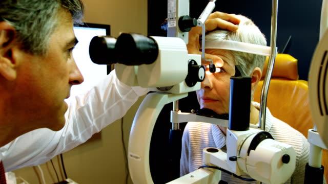 Optometrista, examinando os olhos do pacientes com lâmpada de fenda 4k - vídeo