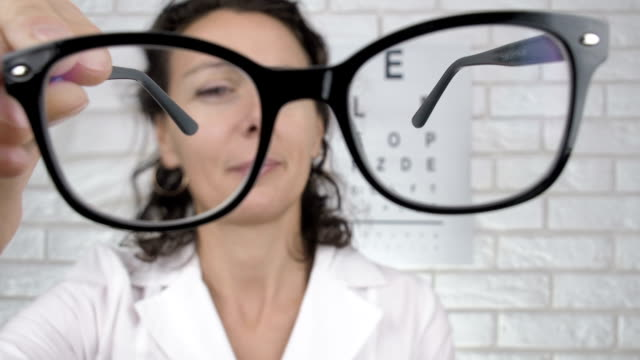 Optometrist shows glasses. Optometrist shows glasses. Woman doctor with glasses for vision. eye chart stock videos & royalty-free footage