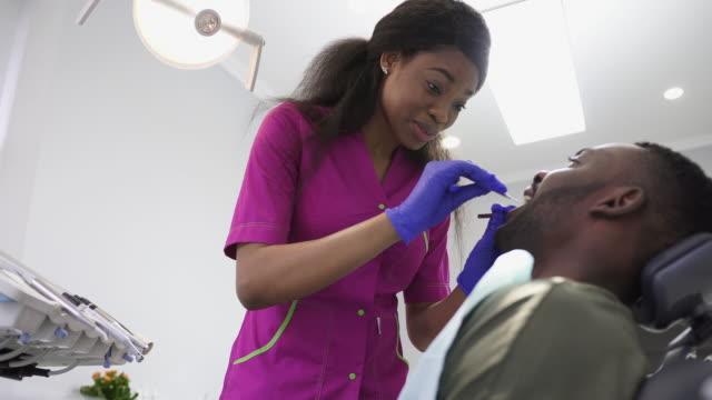 vídeos y material grabado en eventos de stock de higiene bucal y cuidado dental. bastante joven profesional mujer médica doctora dentista trabajando con paciente african american hombre en la clínica dental. de cerca - ortodoncista