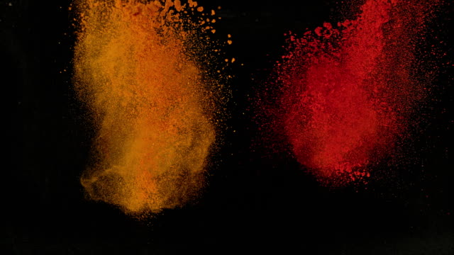 SLO MO LD Orange and red powdered spices exploding out of black background Slow motion medium locked down shot of an orange and red powdered spice exploding and emerging from the black background. Shot in Slovenia. spice stock videos & royalty-free footage