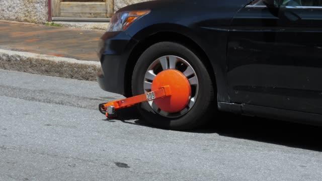 orange boot on parked car - proibizione video stock e b–roll