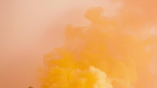 vídeos de stock e filmes b-roll de orange colored smoke on a white background. - laranja cores