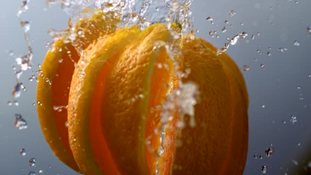 orange falling apart into slices. super slow motion - gusto aspro video stock e b–roll