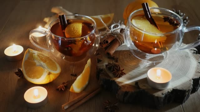 Orange flavored tea with cinnamon and cardamom in cup, orange and cinnamon sticks lit by candlelight on a wooden table. Mulled wine and spices on wooden background. Selective focus. Close up.