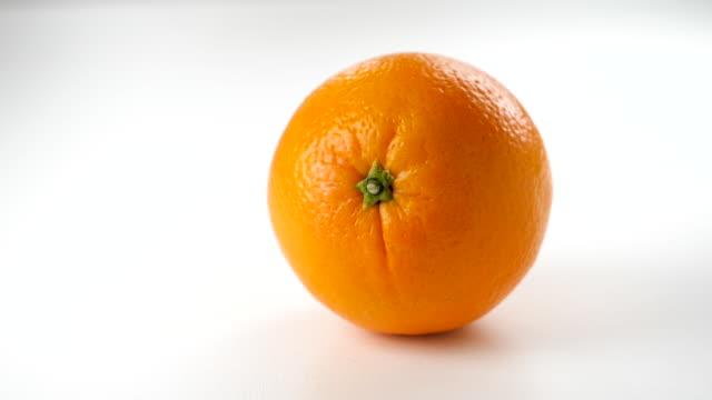 orange fruit falling slow motion on white background