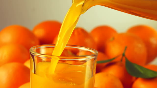 orange juice being poured into glass, slow motion video