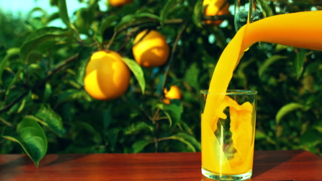Orange juice is poured from a jug into a glass
