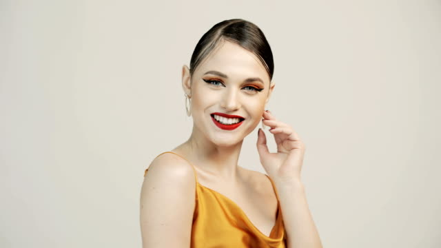 Orange makeup. Woman smiling and posing for the camera. Young beautiful girl with orange eyeshadow and red lipstick. Orange makeup. Woman smiling and posing for the camera. Silver earrings, jewelry. Beauty salon. eyeliner stock videos & royalty-free footage