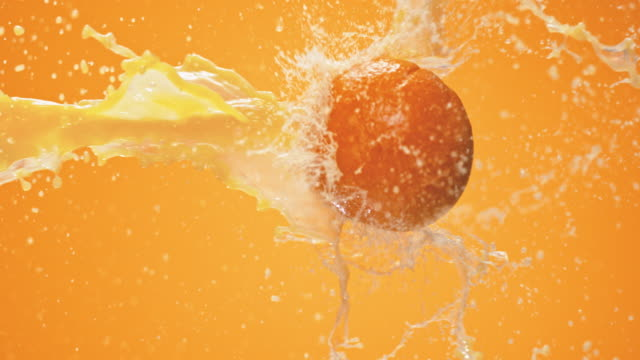 SLO MO Orange meeting juice splash in the air Slow motion locked down close up shot of an orange meeting a juice splash in the air on an orange background. orange juice stock videos & royalty-free footage