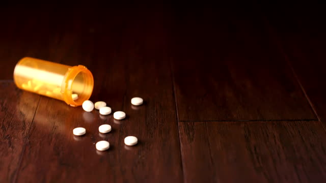 Orange Pill Bottle Falls on Left Side Slow Motion a prescription orange bottle falls on the left side and some white pills spill out of the opening on a wooden surface. Slow motion bottle stock videos & royalty-free footage
