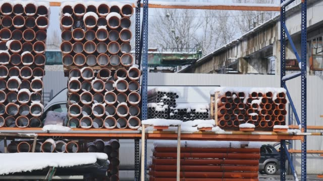 Orange PVC pipes stacked in construction site video