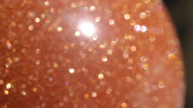 MACRO DOF: Orange semi precious sunstone gem coming in and out of camera focus. video