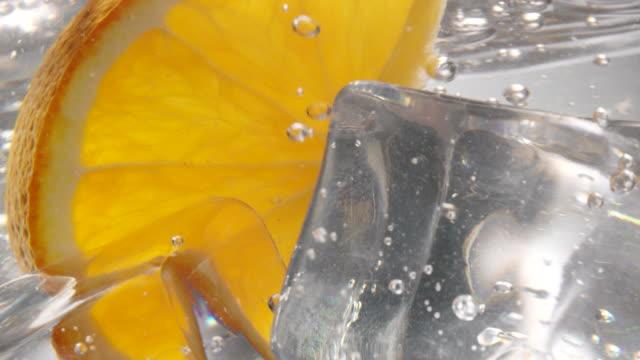 orange skiva faller ner i vatten med isbitar i det - apelsin bildbanksvideor och videomaterial från bakom kulisserna