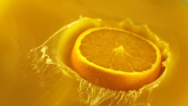 Orange slice falls in juice