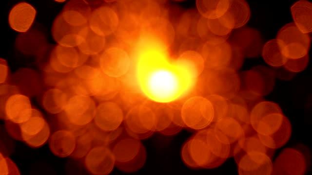 Orange sparkler against dark background, bokeh video. Super slow motion, 500 fps
