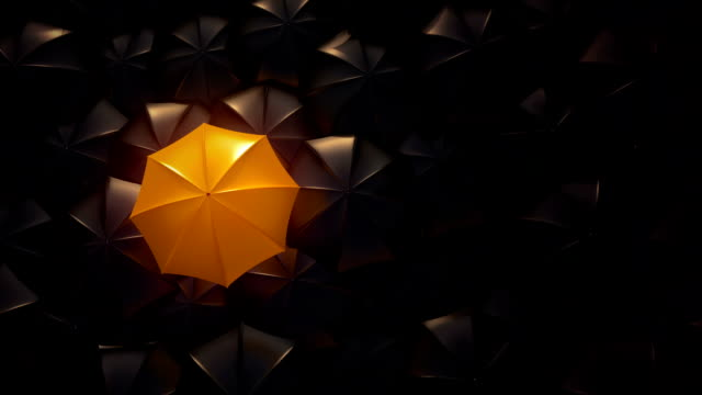 Orange umbrella standing out from crowd mass concept