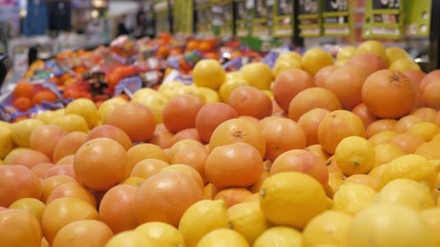 vidéos et rushes de oranges, pamplemousses et citrons au supermarché. citrus assortis - pamplemousse