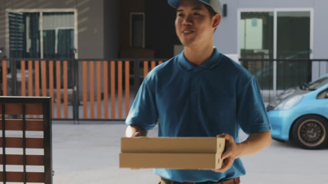 Order food online and Delivery Service concept. Delivery man in uniform or courier delivers pizza to young woman customer at front of her house. 4K footage resolution. Order food online and Delivery Service concept. Delivery man in uniform or courier delivers pizza to young woman customer at front of her house. 4K footage resolution. post office stock videos & royalty-free footage