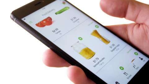 vídeos de stock e filmes b-roll de ordering food online using smartphone app - food