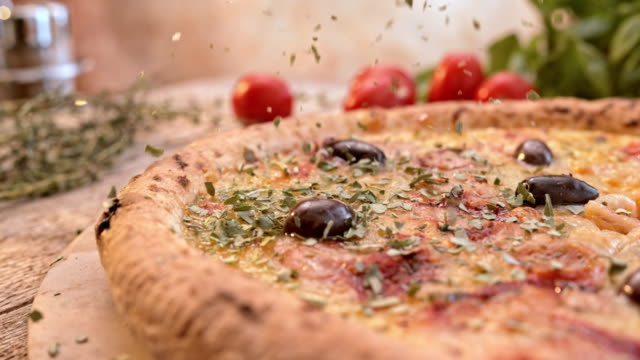 SLO MO Oregano falling on a cheese and olives pizza video