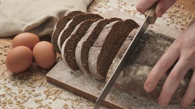 bio-brot auf holzbrett mit eiern. schneiden von brot auf holzschneidebrett. - vollkorn stock-videos und b-roll-filmmaterial