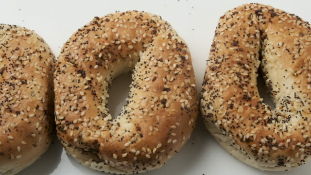 organic everything bagels from above on white background - sesamo video stock e b–roll