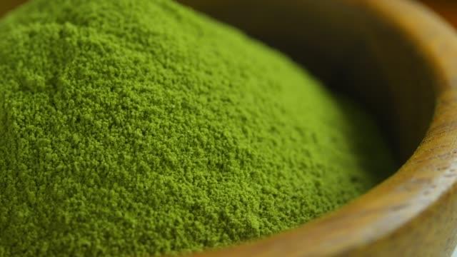 bio matcha grüntee-pulver in holz schüssel - gemahlen stock-videos und b-roll-filmmaterial