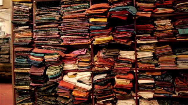 oriental abbigliamento/materiale scaffali nel negozio - industria tessile video stock e b–roll