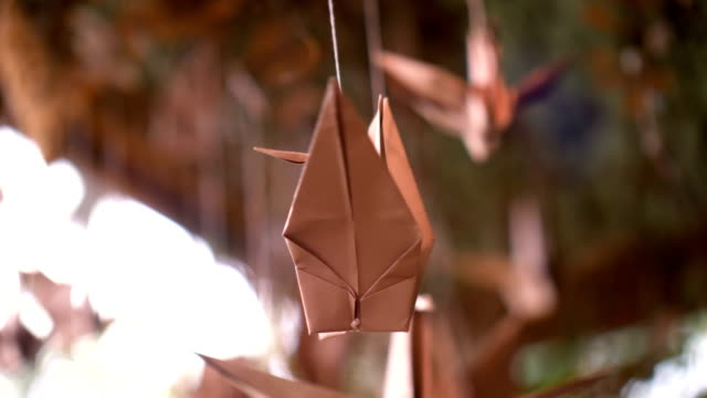 origami of bird paper craft hanging closeup, unique paper toy turning around in wind for decoration, creativity - stock video - япония стоковые видео и кадры b-roll
