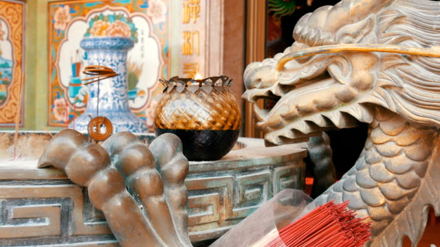 Original candlestick in Chinese style. Bronze statue of a dragon and a burning candle near video
