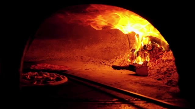 Original Italian pizza in a traditional wood oven in Italy Original Italian pizza in a traditional wood oven in Italy. Cooking pizza in oven in slow motion. margarita stock videos & royalty-free footage