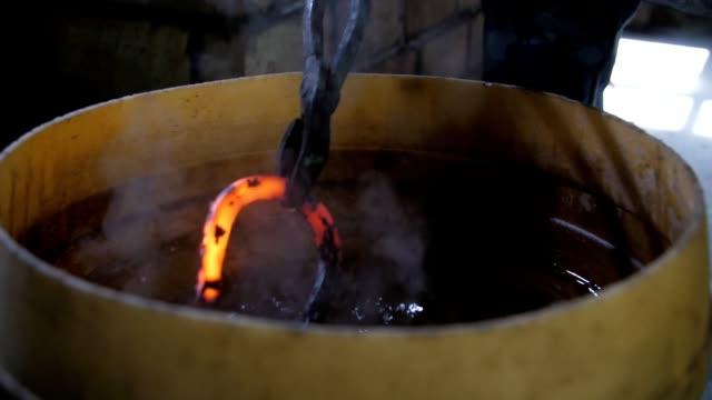 vista originale di un ferro di cavallo messo in una grande pentola rotonda con cera d'api per raffreddare il suo ferro rosso in un laboratorio di fabbro. fa molto vapore. - fabbro ferraio video stock e b–roll