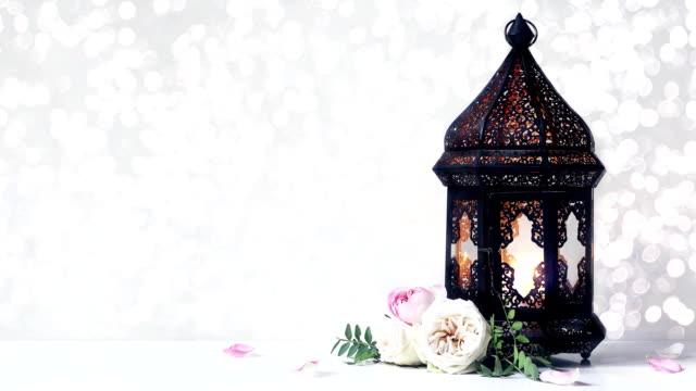 vídeos y material grabado en eventos de stock de linterna morrocan ornamental, vela ardiente, rosas flores y pétalos sobre mesa blanca. centelleante luces bokeh. fondo festivo. vacaciones musulmanas ramadán kareem, eid ul fitr imágenes hd. - eid mubarak