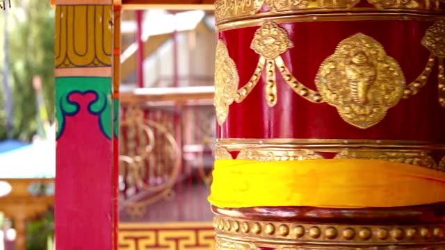 Ornate Tibetan prayer wheel spinning in the monastery in Northern India video