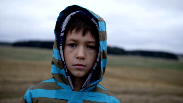 orphan emaciated refugee boy stands alone looking into the camera video