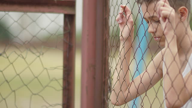 orphan refugee boy stands alone head bowed near the fence video