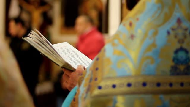 vídeos y material grabado en eventos de stock de clérigo de la iglesia ortodoxa leyendo libro de salmo, realizando servicio de fiesta, oración - misa