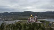 istock orthodox church on the bank of the Yenisei river. Aerial photography from a quadrocopter in motion 1318667561