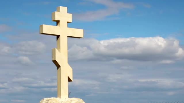 Orthodox stone cross against blue sky background, belief in God, video