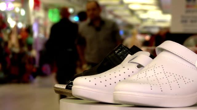 vídeos y material grabado en eventos de stock de zapatos ortopédica, sobre un fondo de las compras centro comercial. multitud de personas que compran. - columna vertebral humana